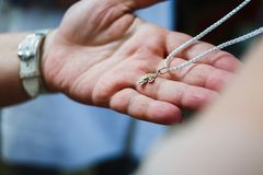 Cross in the father`s hand. Orthodox christenings of a child, a cross in his father`s hand Stock Photos