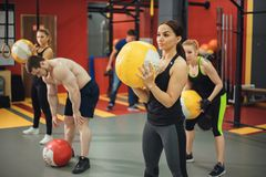 Workout group woman and man at gym. Cross fit ball fitness workout group women and men at gym. camera focus in the ball Stock Photo