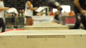 Cross Fit event, jumping on box. Close up slow motion footage of people jumping on box at Cross Fit event stock video