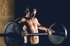 Man lifting weights. muscular man workout in gym doing exercises with barbell. Cross fit fitness gym heavy weight lifting bar by strong man workout Royalty Free Stock Image