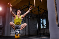 Cross fit fitness man standing and balance on the kettlebells in the gym against brick wall. Sportsman in the sportwear, yellow t-shirt, shorts and sportive Stock Photos