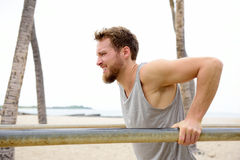 Cross fit man working out doing dips exercises. Strength training for arms outside on beach on fitness outdoor gym station royalty free stock image