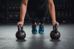 Cross fit training with kettleballs. Athlete woman doing push ups on two kettlebells Royalty Free Stock Image