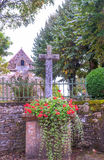Cross with flowers. And a church in the background in Aquitaine, France. It is a vertical image on a cloudy day Royalty Free Stock Photo