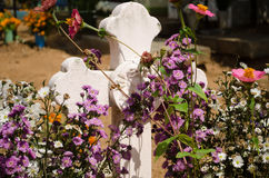 Cross with flowers. Cross of a grave with flowers Royalty Free Stock Photos