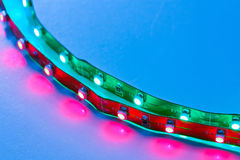 Cross frame LED Lighting. Close up of LED lighting strips illuminated against blue background with very narrow depth of field. Printed circuitry clearly seen royalty free stock images