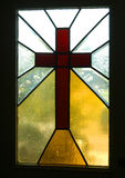 Cross framed  in Stained Glass. Cross is displayed in stained glass in a Church Door Stock Images