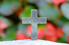 Cross in front of a grave with flowers in the background royalty free stock photography