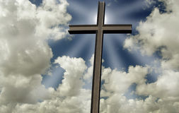 Cross in front of shining sun and clouds Royalty Free Stock Photo
