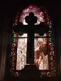 Cross in front of a stained glass Stock Images