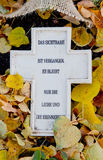 Cross with german text at the grave in autumn Stock Image