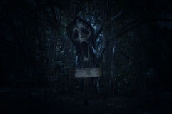 Cross with ghost scream over spooky forest at night time Stock Image