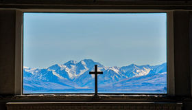 Cross of the Good Shepherd. Cross is silhouetted against the Mount Cook Mountain Range in the Church of the Good Shepherd in Lake Tekapo, New Zealand Royalty Free Stock Image