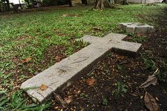 Cross on grave. Old stone cross on grave. Green grass in background Royalty Free Stock Photo