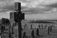 Cross Gravestone. Celtic cross overlooking an old graveyard with coastline in the background stock photography