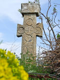 Cross Gravestone, Romania. Old and forgotten cross gravestone with wild flowers growing, Romania Royalty Free Stock Images