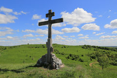 Cross on green hill. In sunny day Stock Photo