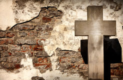 Cross and grunge wall on cemetery Stock Photos
