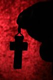 Cross in hand. Cross in his hand against the red background Royalty Free Stock Photo