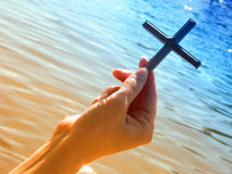 Cross in hand. Female hand keeping cross above watery surface stock images