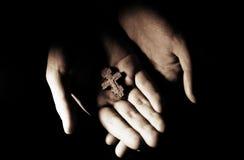 Cross in hands. Wooden cross in believer's hands,in soft light Stock Image