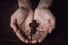 Cross hands. Wooden cross into the hands of men Stock Photos