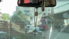 Cross hanging from the mirror in the car.  stock footage