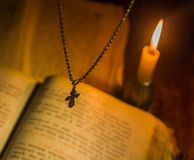 The cross hangs over a prayer book with a burning candle Stock Photography