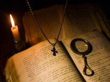 The cross hangs over a prayer book with a magnifying glass Stock Photo