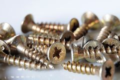 Cross-head screws. Macrophotography of brass screws with cross-drive heads Royalty Free Stock Images