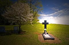 Cross headstone on grave. Cross on a grave headstone in a small country cemetery in spring Stock Images