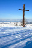 Cross on a hill. A wooden cross on the top of a snowy hill Royalty Free Stock Image