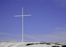 Cross on hill in northern Canada. A single cross on a hill oitlined against the blue sky at Dettah a First Nations village near Yellowknife, NWT, Canada Stock Photos