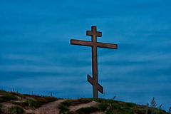 Cross on the hill. In reflection of the setting sun Stock Images