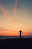 Cross on hill at sunset. Christian cross against dawn and clouds Stock Image