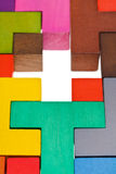 Cross hole in wood multicoloured puzzle. Cross shape hole in wooden multicoloured puzzle Stock Photo