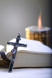 Cross and Holy Bible. Old Cross and the Holy Bible laying on the table in fornt of a lighting candle Stock Photos