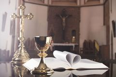 First holy communion theme. Catholic concept background. The Cross, Holy Bible, rosary and golden chalice on the altar.  Place for typography or logo Royalty Free Stock Photography
