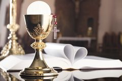 First holy communion theme. Catholic concept background. The Cross, Holy Bible, rosary and golden chalice on the altar.  Place for typography or logo Royalty Free Stock Images