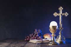 First holy communion theme. Place for typography or text. The Cross, Holy Bible, rosary and golden chalice. Bread and grapes – symbols of Christianity royalty free stock images