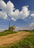 Cross on the horizon. Cross over the village with dirt roads Royalty Free Stock Image