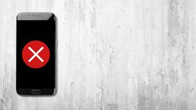 Cross icon on black smartphone on white wooden background royalty free stock image