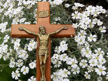 Cross with Jesus Christ on tiny white flowers. Crucifix laying in patch of small white Snow in Summer flowers. Concept that though our sins are as scarlet Jesus royalty free stock photo