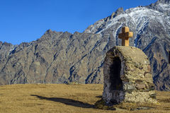 Cross in Kazbegi with view of caucasus. Cross in Kazbegi with view of caucasus Royalty Free Stock Photo