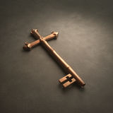 Cross Key. An old fashioned brass key laying on white surface shaped like a cross Stock Photos