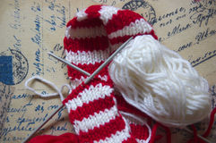 Cross knitting needles. Skeins of wool and knitting needles for made a red and white textile scarf with golden background stock photo