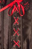 A corset with a red ribbon. Cross-lacing on black silk. Red lace, scarlet ribbon. women`s underwear, role-playing games, passion in bed. Vertical arrangement royalty free stock photo