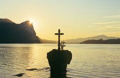 Cross on lake. On a rock on an austrian lake is a cross like on a tomb. the golden rays of the sun behind a rocky hill in the background is like the divine light Royalty Free Stock Photo