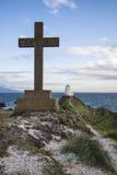 Cross in landscape of Ynys Llanddwyn Island with Twr Mawr lighthouse in background with blue sky. Cross in landscape of Ynys Llanddwyn Island with Twr Mawr stock photo