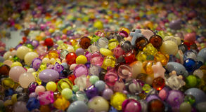 A cross lays in the colorful beads. Stock Photos
